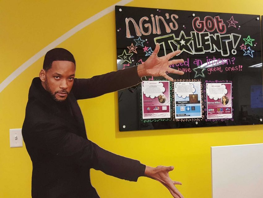 Will Smith cardboard cutout placed in front of an NGIN Workplace Boston Coworking Space Bulletin Board advertising NGIN's Got Talent
