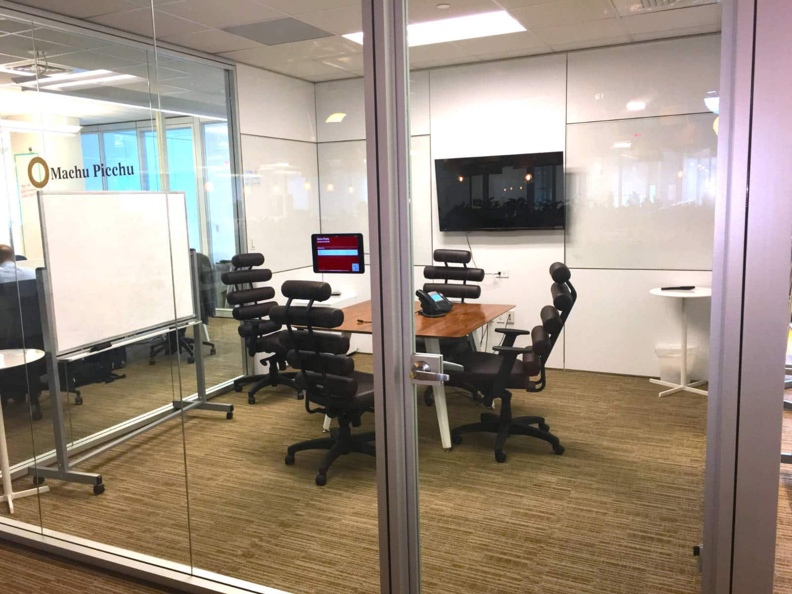 Shot from outside the Machu Picchu meeting room, looking in through the glass walls. Focus is on the square table with 4 modern, black chairs surrounding the table and the flat screen monitor on the walls.