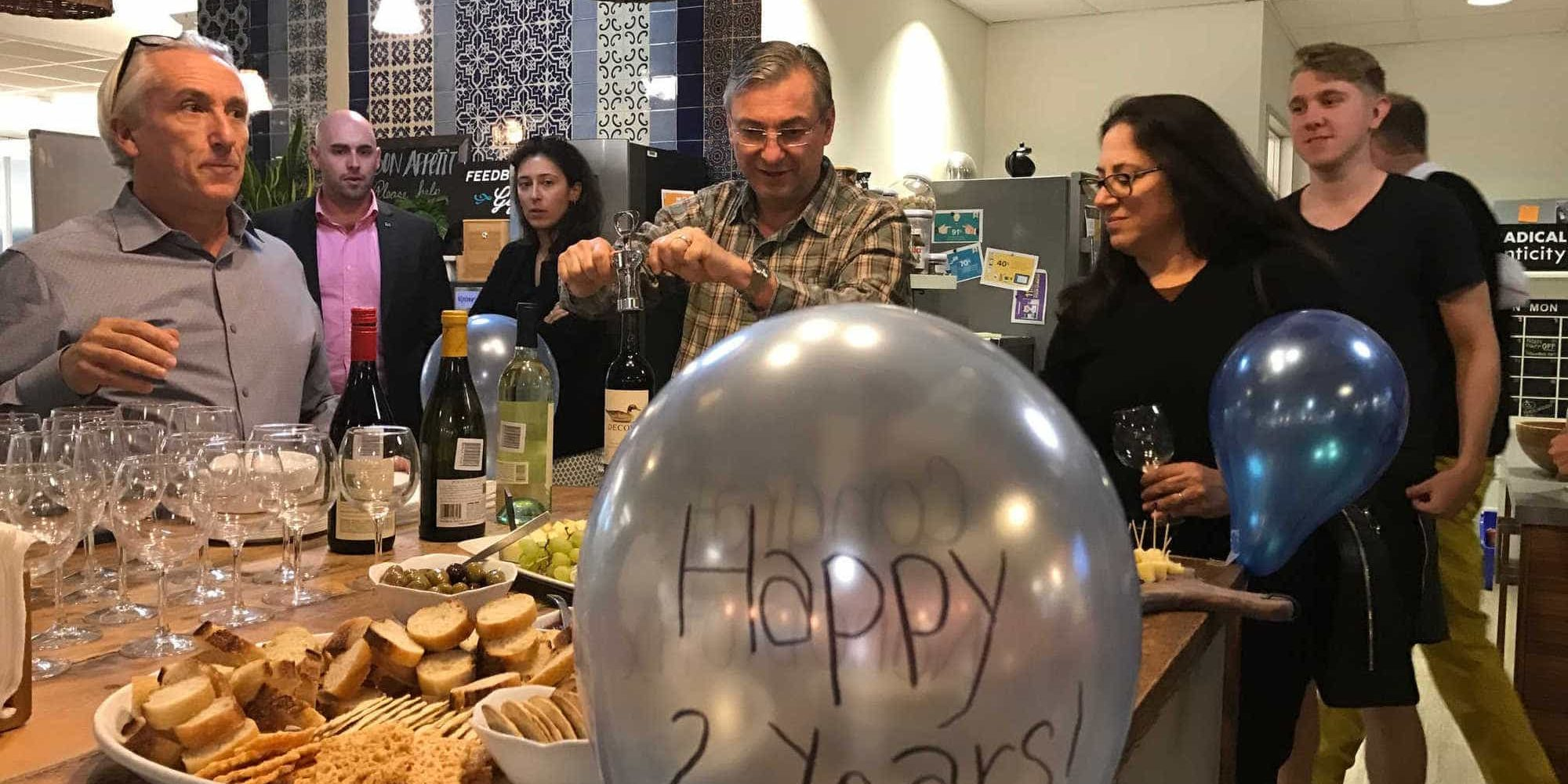 Many members celebrating a 2 year anniversary in NGIN Workplace's kitchen and dining area, with food, wine, and balloons.