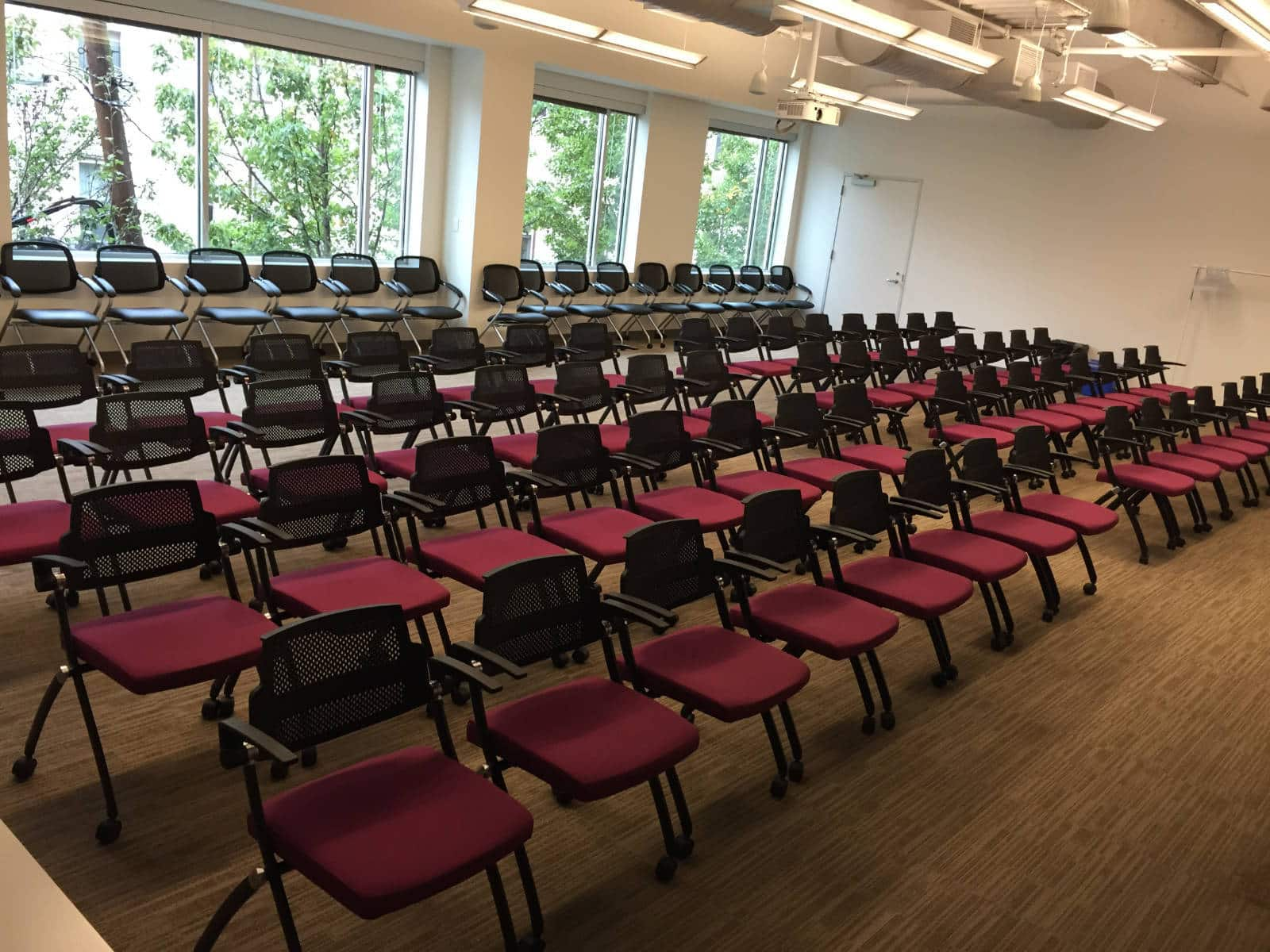 Five rows of chars lined up in a classroom or theatre style arrangement in NGIN Workplace's conference room.