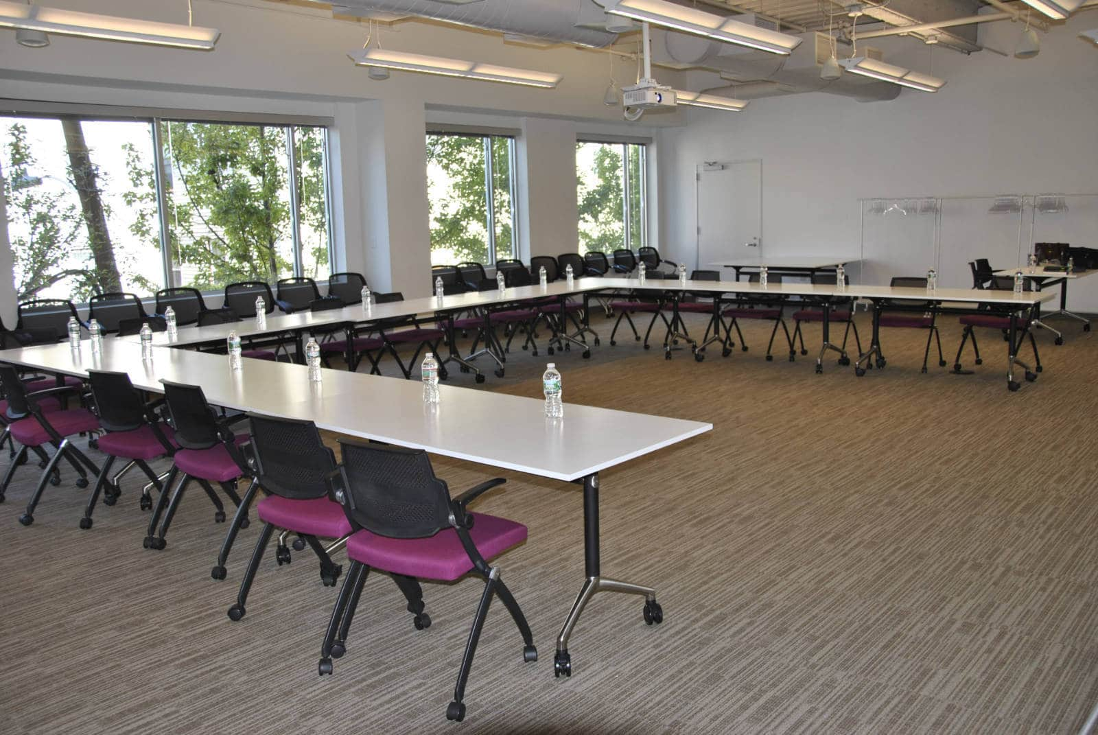 Interior shot of a large, empty conference room space. White walls and large white tables with purple chairs and bottles of water lined up at each place.