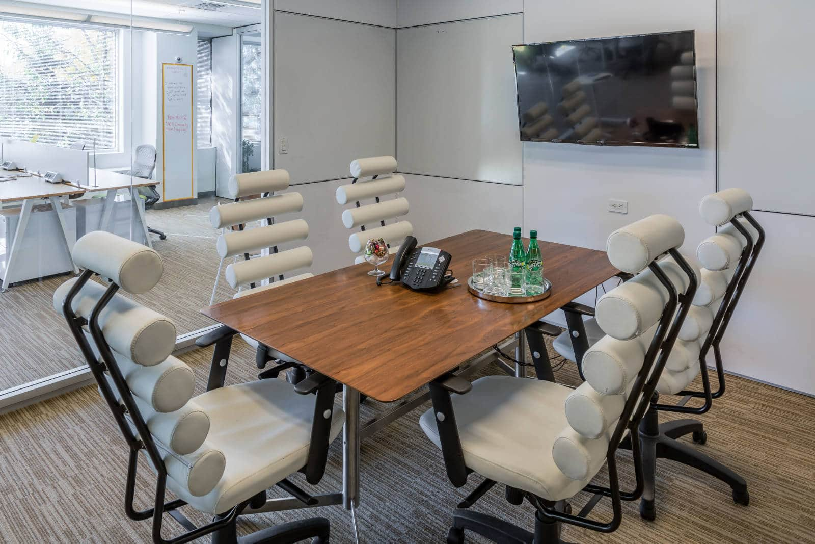 Interior shot of a meeting room with large, modern white chairs, and a beautiful, modern table and flat screen TV