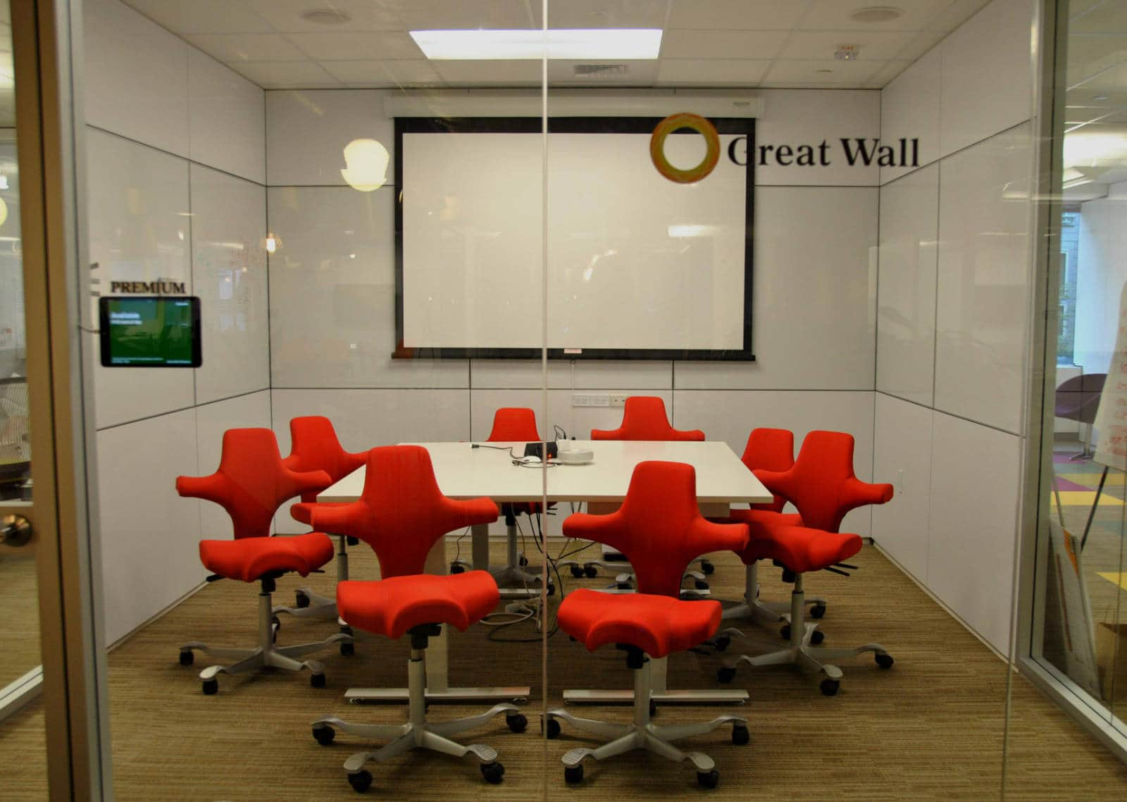 From outside the meeting room, looking through the glass walls, a large white table, with several very modern looking red chairs, a projector, and white walls.